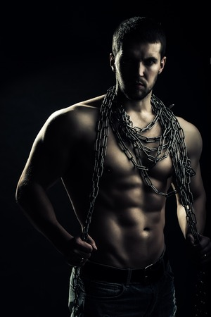 sexual anatomy: One handsome sexual strong young man with muscular body in blue jeans holding rope with hands hanging on neck and shoulders standing posing in studio on black background, vertical picture Stock Photo