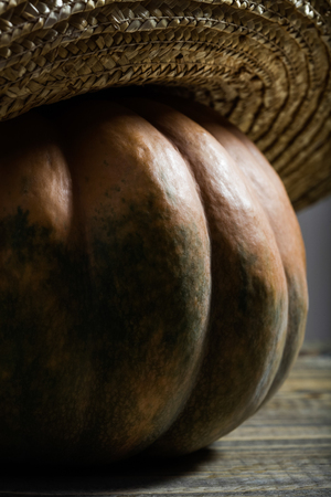 flaps: Photo rustic autumn still life closeup one side of big whole fresh orange pumpkin in feminine straw hat with wide flaps broad brim on wooden table on timber background, vertical picture Stock Photo