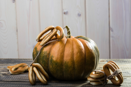 hard bound: Photo closeup rustic autumn still life one big whole fresh orange pumpkin with bunches of hard oval cracknels bind with string on wooden table on timber background, horizontal picture