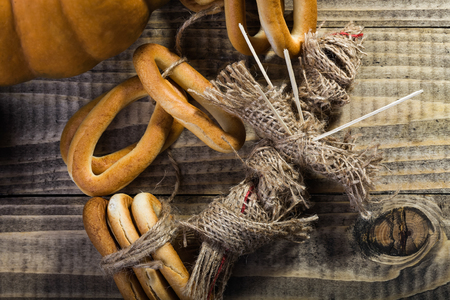 bind: Photo top view still life partial orange pumpkin bunches of hard oval cracknels bind with string and voodoo doll with sticks on chest laying on wooden table on timber background, horizontal picture Stock Photo