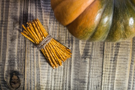 string together: Photo top view sheaf of delicious stick biscuits straws tied together with string and one side of big whole fresh orange pumpkin on wooden table on timber background, horizontal picture Stock Photo