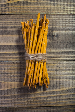 food products: Photo top view bread and flour products one sheaf of delicious stick biscuits straws tied together with string laying on wooden table on timber background, vertical picture
