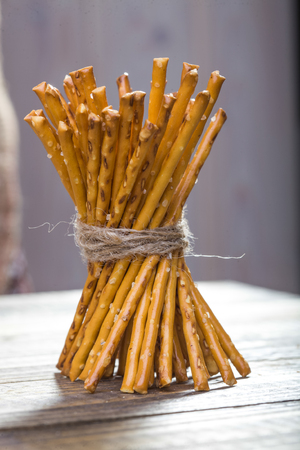string together: Photo closeup of bread and flour products one sheaf of delicious stick biscuits straws tied together with string standing on wooden table on blurred rustic background, vertical picture