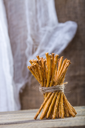 string together: Photo of bread and flour products one sheaf of delicious stick biscuits straws tied together with string standing on wooden table on blurred rustic background, vertical picture