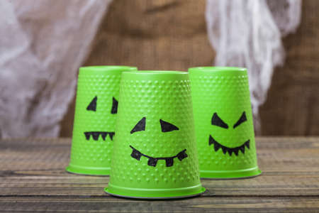 phantom: Photo set of three green disposable cups with Halloween ghost scary faces smiles with teeth drawn in black felt pen standing on wooden table over blurred rustic background, horizontal picture Stock Photo
