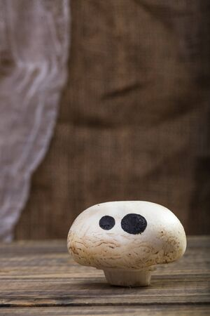 button mushroom: Photo closeup still life of one Halloween white button mushroom champignon with ghost face eyes drawn in black felt pen standing on wooden table over blurred rustic background, vertical picture