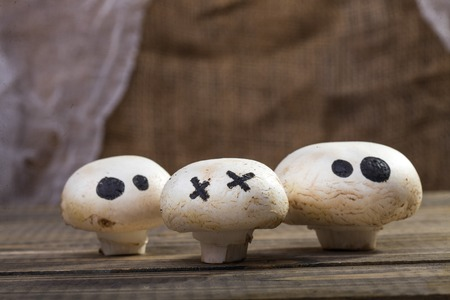 ghost face: Photo still life set of three Halloween white button mushrooms champignons with ghost face eyes drawn in black felt pen standing on wooden table over blurred rustic background, horizontal picture Stock Photo