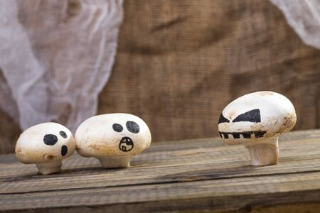 ghost face: Photo still life set of three Halloween white button mushrooms champignons with ghost face smiles drawn in black felt pen standing on wooden table over blurred rustic background, horizontal picture