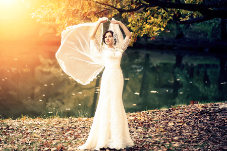 bride: Full length view of one beautiful sensual young brunette bride in long white wedding dress and veil standing near river in autumn leaves outdoor on natural background, horizontal picture