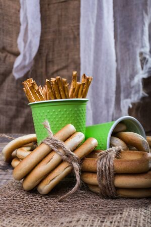 peaking: Still life two green disposable cups containing stick biscuits hard oval cracknels and bunches bind with string lying on sackcloth wooden table on rustic background, vertical picture Stock Photo