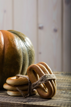 hard bound: Photo closeup rustic autumn still life partial fresh orange pumpkin with bunches of hard oval cracknels bind with string on wooden table on timber background, vertical picture Stock Photo