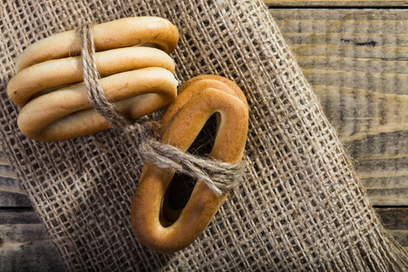 string top: Photo top view closeup groups of delicious hard oval cracknels bind with string in bunches in threes laying sackcloth coarse fabric on wooden table over rustic background, horizontal picture Stock Photo