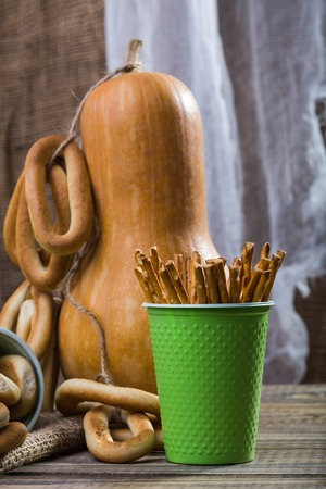 bind: Still life closeup one big gourd with bunches of hard oval cracknels bind with string and disposable green cup with straws standing on wooden table on blurred rustic background, vertical picture Stock Photo