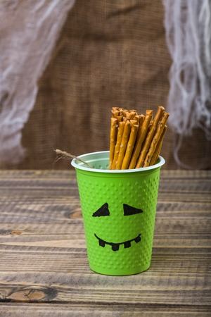 peaking: Photo still life one disposable green cup with Halloween ghost face drawn in black felt pen containing straws peaking out standing on wooden table over blurred rustic background, vertical picture