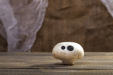 button mushroom: Photo still life of one Halloween white button mushroom champignon with funny ghost face eyes drawn in black felt pen standing on wooden table over blurred rustic background, horizontal picture