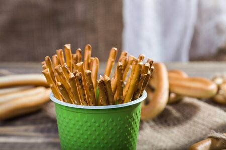 peaking: Photo closeup still life one disposable green cup containing stick biscuits straws peaking out and hard oval cracknels lying on tablecloth on blurred rustic background, horizontal picture