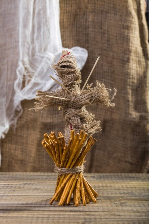 string together: Photo still life of one sheaf of delicious stick biscuits straws tied together with string and voodoo doll with sticks on chest standing on wooden table on blurred rustic background, vertical picture Stock Photo