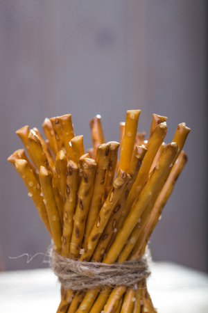 string together: Photo closeup of bread and flour products half of one sheaf of delicious stick biscuits straws tied together with string on blurred grey background, vertical picture Stock Photo