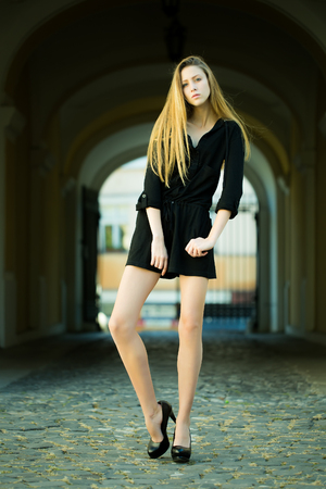 sidewards: Portrait of pretty blond girl with straight long hair flowed over her shoulders posing in black casual short dress high heels full length standing on pavement on archway background, vertical picture Stock Photo