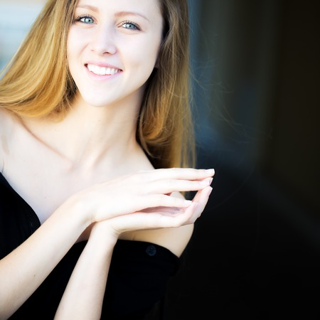 bare shoulders: Portrait closeup of smiling pretty blond girl with long hair big joyful smile locking finger pads posing in black bare shoulders outside on blurred background, square picture