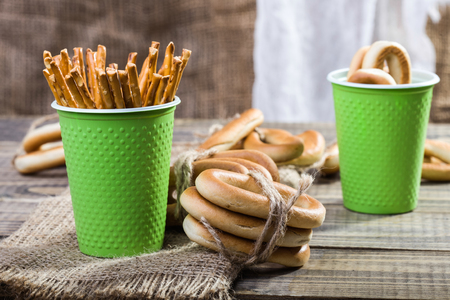 peaking: Still life two disposable green cups containing stick biscuits hard oval cracknels and bunches bind with string lying on sackcloth wooden table on rustic background, horizontal picture Stock Photo