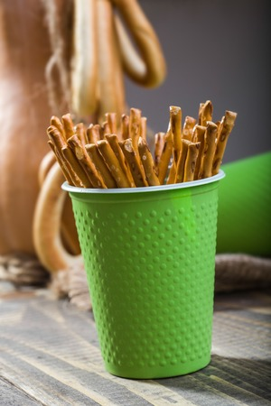 bind: Still life one disposable green cup containing straws standing on wooden table in foreground against blurred partial gourd with bunches of hard cracknels bind with string background, vertical picture Stock Photo