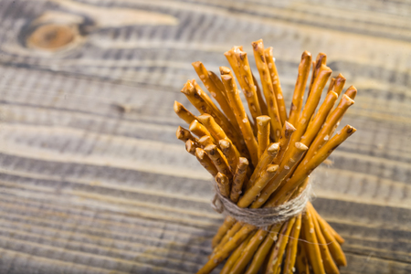string together: Photo top view closeup bread and flour products one sheaf of delicious stick biscuits straws tied together with string on blurred timber background, horizontal picture