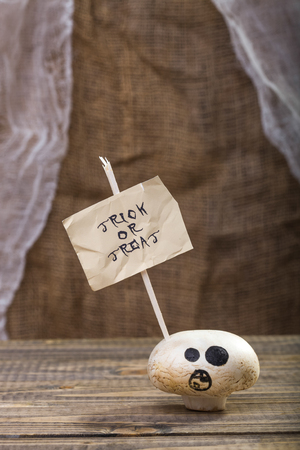 one sheet: Photo closeup still life one white champignon ghost face with happy Halloween lettering trick or treat on white paper sheet on stick on wooden table on blurred rustic background, vertical picture Stock Photo