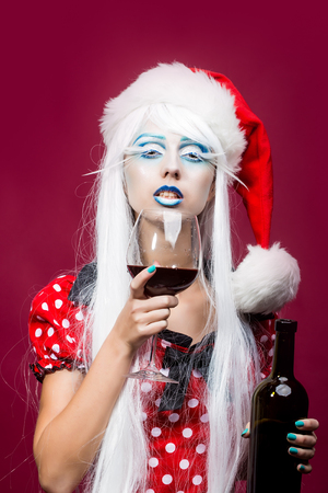 girl models: One beautiful young fairy new year girl with winter blue makeup long white eyelashes and hair wig in red christmas santa hat with cork bottle and red wine glass on pink studio background, vertical