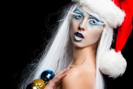 nackt: Eine sch�ne junge Fee neue Jahr nackte M�dchen mit Winter blau Make-up langen wei�en Wimpern und Haarper�cke im roten Kleid und Weihnachten Santa Hut mit Dekoration Kugeln auf schwarzem Studiohintergrund, horizontal