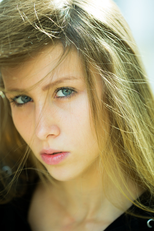 looking towards camera: Portrait closeup of serious pretty blond girl with blue eyes long straight hair sidepart dishevelled falling on face looking towards camera posing outside on ligh background, vertical picture Stock Photo