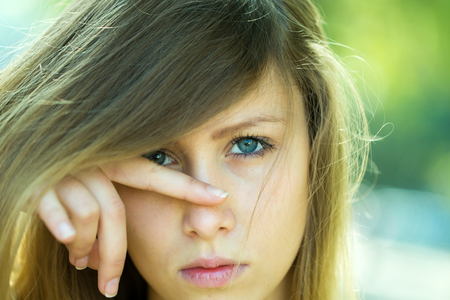 blonde yeux bleus: Portrait agrandi grave jolie blonde yeux bleus fille avec de longs cheveux raides partie latérale de tomber sur le visage doigt sur le nez regard caméra vers l'avant en dehors posant sur fond ligh floue, l'image horizontale Banque d'images