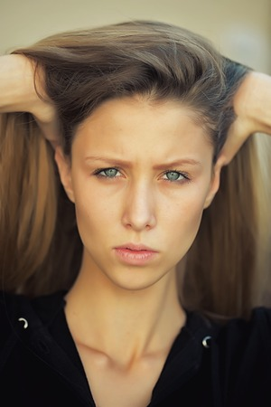 sidewards: Portrait closeup of pretty blond girl lips pursed frowning face with blue eyes straight long hair pinning hands to head posing in black outdoors on grey background, vertical picture