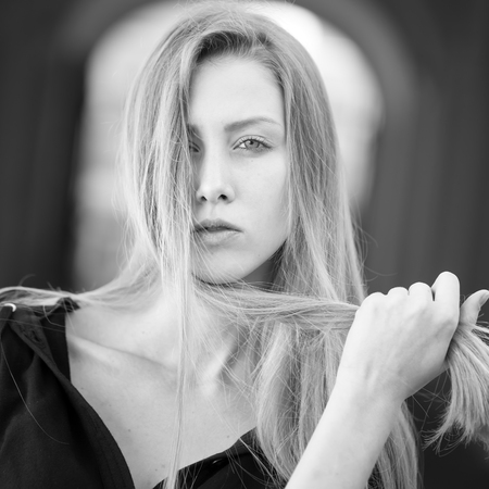 sidewards: Closeup portrait of one beautiful serious cool blonde young woman with long hair outdoor looking forward on blurred background black and white, square picture