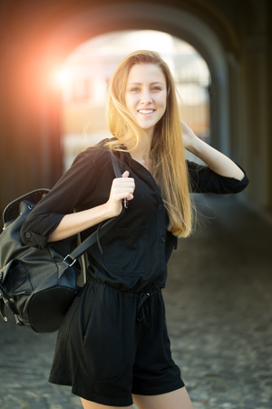 mouth smile: One beautiful smiling cute young blonde stylish straight woman in sportive black dress with hood and long hair holding big bag on shoulder standing in arch on outdoor background, vertical picture