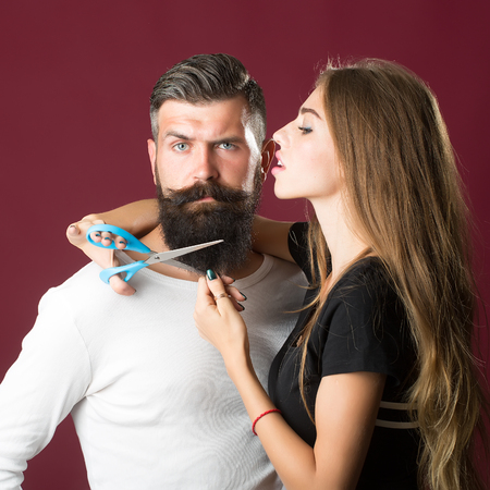 long beard: Closeup view of young beautiful couple of beautiful female barber cutting with scissors long beard of handsome man in studio on purple background, square picture