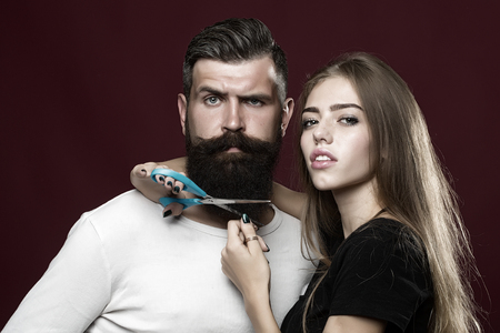 studio model: Closeup view of young beautiful couple of beautiful female barber cutting with scissors long beard of handsome man in studio on purple background, horizontal picture Stock Photo