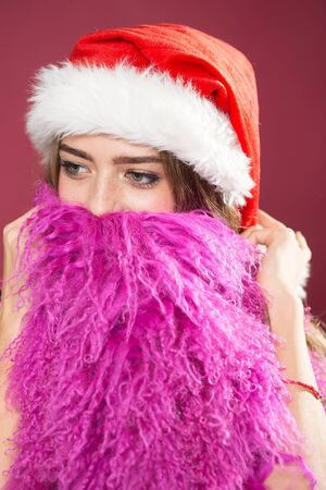 long beard: Closeup portrait of one beautiful young surprised new year woman in red santa christmas hat with fur and lilac waistcoat as long beard in studio on purple background, vertical picture Stock Photo