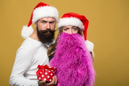 long beard: Young beautiful happy new year couple of man with long beard with present box and woman in red santa christmas hat with fur in studio on yellow background, horizontal picture Stock Photo