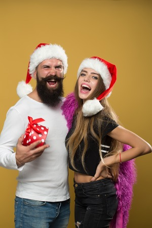 long beard: Young beautiful happy new year couple of man with long beard with present box and woman in red santa christmas hat with fur in studio on yellow background, vertical picture