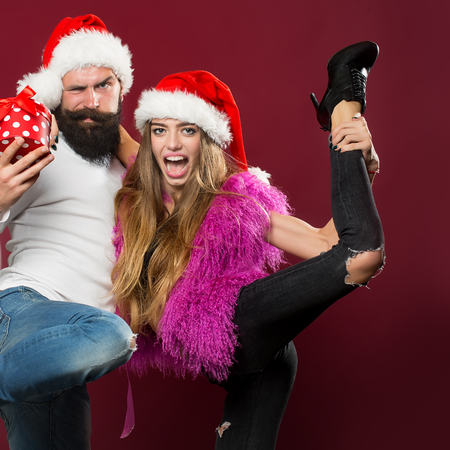 long beard: Young beautiful happy new year couple of man with long beard with present box and woman in red santa christmas hat with fur in studio on purple background, square picture