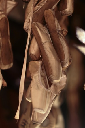 balletic: Closeup view of many beautiful pink silk female ballet shoes of points with ribbon hanging as decoration toys, vertical picture