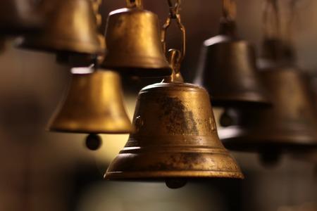 campanas: Vista de cerca de muchas hermosas viejas campanas de navidad de oro colgando de moda como juguetes del Año Nuevo, cuadro horizontal