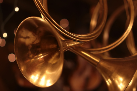 Closeup view of few shiny yellow golden wing musical instrument5 of horn as christmas little toys, horizontal picture