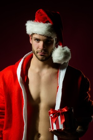 male costume: Closeup portrait of one handsome sexy new year young muscular man with bare chest in red christmas santa claus winter coat with hood holding present box on pink studio background, vertical picture Stock Photo
