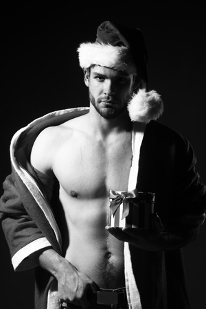 young man portrait: Closeup portrait of one handsome sexy new year young muscular man with bare chest in christmas santa claus winter coat with hood holding present box in studio black and white, vertical picture Stock Photo