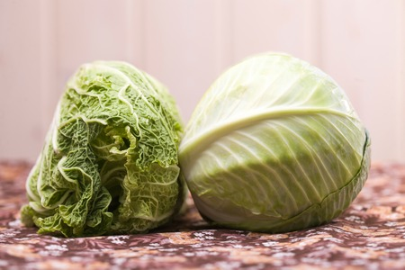 two heads: Two heads of rustic tasty juicy eco cole and chinese cabbage vegetable laying on floral tablecloth indoor on blur light background closeup, horizontal picture