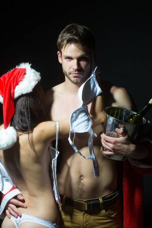 red corset: Young sexual new year couple of woman in corset and red christmas hat embracing muscular man in santa claus winter coat holding wine bottle with cork in pail in studio on black background, vertical