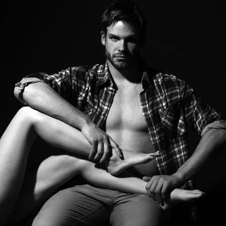 a pair of: One sexual muscular man in open checkered shirt sitting holding straight beautiful long female legs in studio black and white, square picture