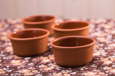 materia prima: Four beautiful pottery artwork authentic bowls made of ecological raw material standing on floral background indoor closeup, horizontal picture